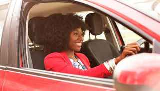 Young person driving red car and smiling