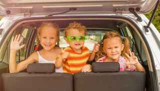 Three children in the back seat of a car