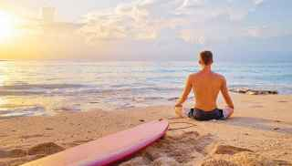 Man meditating on beach next to surfboard