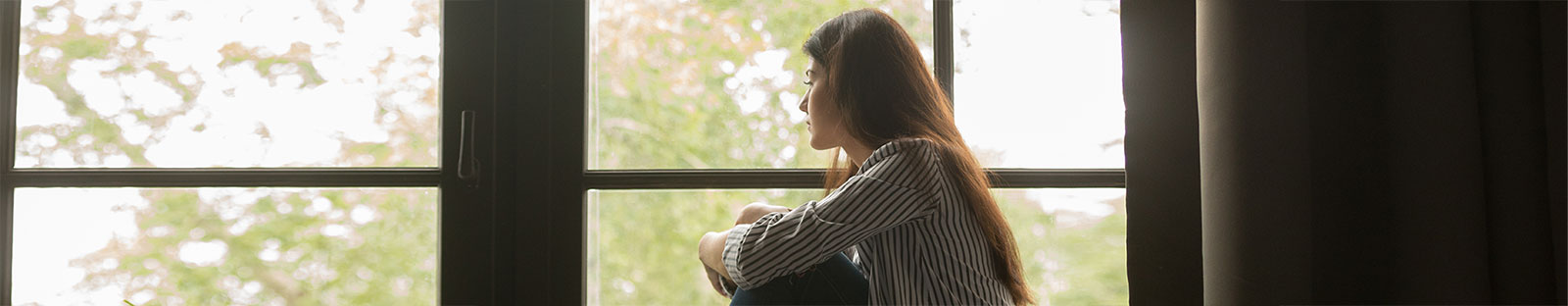 Thoughtful woman sitting on sill embracing knees looking at window